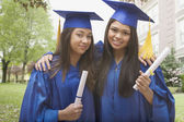 Multi-ethnic girls holding diplomas and hugging — Stock Photo