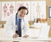 Asian male doctor writing at desk — Stock Photo