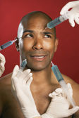 African American man receiving injections in face — Stock Photo