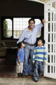 Hispanic father and sons in doorway — Stockfoto