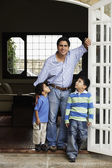 Hispanic father and sons in doorway — Stock Photo