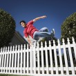 Hispanic man jumping over fence — Stock Photo #52080275