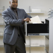 Businessman looking in file cabinet — Stock Photo #52081319