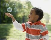African boy catching bubbles — Stock Photo