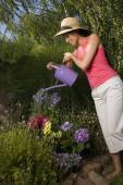Mixed Race woman watering flowers — Stock Photo