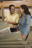 Multi-ethnic couple looking at flooring samples — Stock Photo