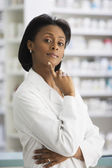 African female pharmacist with finger on chin — Stockfoto