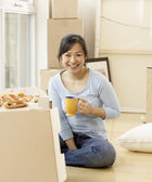 Asian woman surrounded by moving boxes — Stock Photo