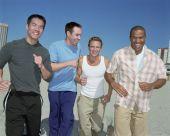 Multi-ethnic men running on beach — Stock Photo