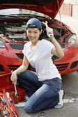 Asian woman fixing car — Stock Photo