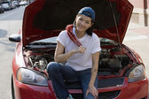 Asian woman sitting next to open car hood — Stock Photo