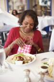 Senior African American woman opening gift bag at restaurant — Foto Stock
