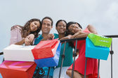 Hispanic friends holding shopping bags — Stock Photo