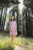 Asian girl standing in woods — Stockfoto