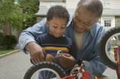 African grandfather and grandson fixing bicycle — Stock Photo