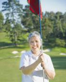 Senior Asian woman holding golf flag — Foto de Stock