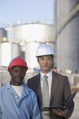 Businessman and construction worker wearing hardhats — Stock Photo