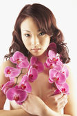 Nude Asian woman holding flowers over breasts — Stock Photo