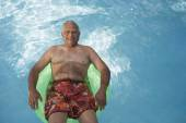 Senior Mixed Race man floating in swimming pool — Foto Stock
