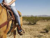 Hispanic woman riding horse — Stock Photo