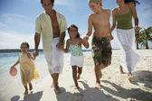 Hispanic family holding hands at beach — Stock Photo