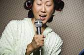 Asian woman in curlers singing — Stock Photo