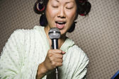 Asian woman in curlers singing — Foto de Stock