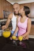 African man pouring orange juice for wife — Stock Photo