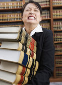 Woman carrying stack of library reference books — Stock Photo