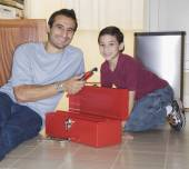 Hispanic father and son looking in tool box — Stock Photo