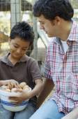 Multi-ethnic father and son with bowl of eggs — Stock Photo