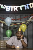 Senior African American male worker with birthday cupcake — Stock Photo