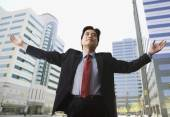 Chinese businessman on city street with arms outstretched — Stock Photo