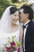Asian groom telling secret to bride — Zdjęcie stockowe