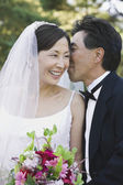 Asian groom telling secret to bride — Стоковое фото