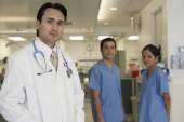 Hispanic male doctor with coworkers in background — Stock Photo