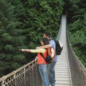 Couple wearing backpacks on footbridge — Stock Photo