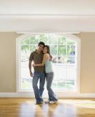 Multi-ethnic couple hugging in new house — Stock Photo