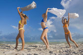 Hispanic women in bikinis holding skirts in wind — Stock Photo
