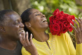 African man surprising wife with flowers — Stock Photo