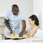 African man serving girlfriend breakfast in bed — Stock Photo