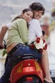 Hispanic couple on scooter — Stock Photo