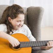 Hispanic girl playing guitar — Stock Photo