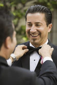 Hispanic man having bowtie adjusted — Stock Photo