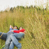 Indian couple laying in tall grass — Stock Photo