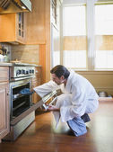 Hispanic man checking food in oven — Stock Photo