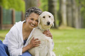 African American woman hugging dog — Stock Photo