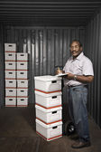 Senior African American male worker with stacks of boxes — Stock Photo