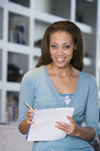 African American woman writing in notebook — Stock Photo