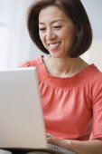 Asian woman looking at laptop — Stock Photo